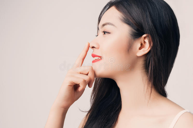 Young beautiful Asian woman with smiley face and red lips touch. Ing her nose royalty free stock photo