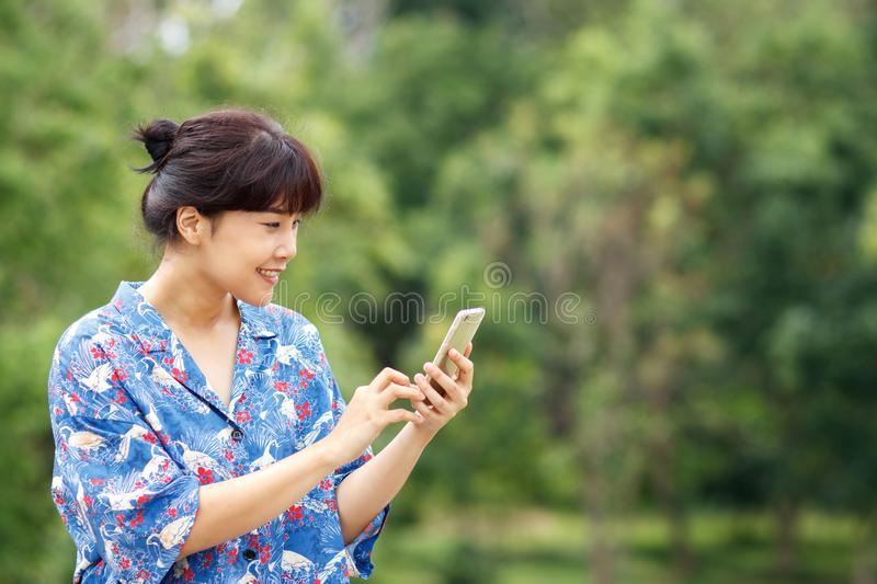 Young beautiful asian woman smiling while reading, typing write stock images