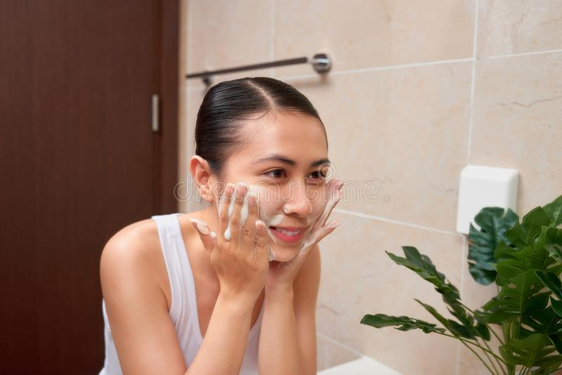 Young beautiful asian woman washing her face with hands by soap stock photo