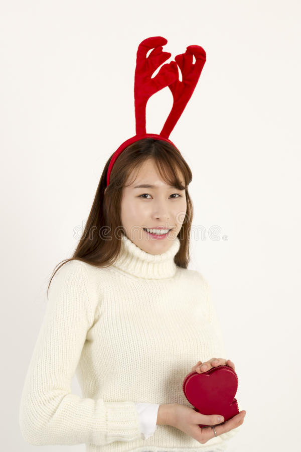 Young beautiful asian woman wearing Christmas antlers. White sweater holding red heart shape stock images