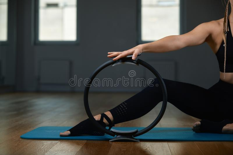 Young, beautiful, athletic girl is doing exercises with the Pilates ring in the gym on a gray background. Sporting stock photo