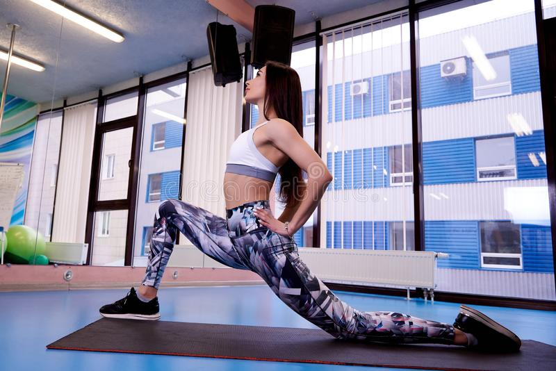 Young beautiful athletic girl exercising sport in the gym stock images