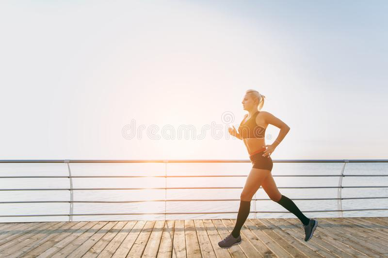Young beautiful athletic girl with long blond hair in black clothes running at sunrise over the sea royalty free stock images