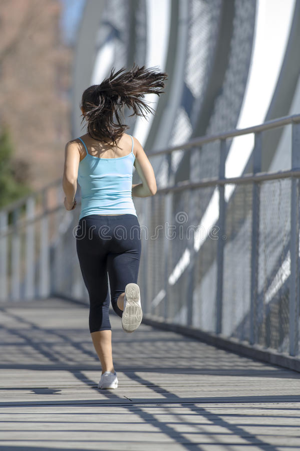 Young beautiful athletic sport woman running and jogging crossing modern metal city bridge. Back view young beautiful and athletic sport woman running and royalty free stock photography