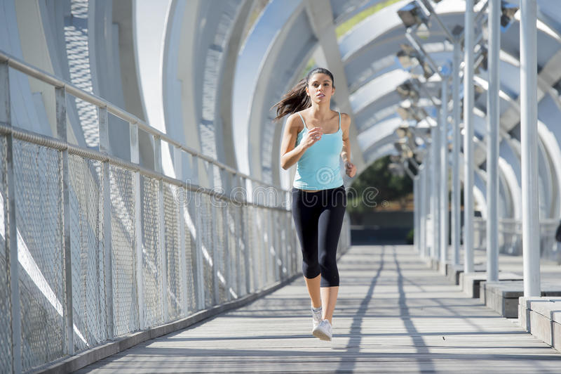 Young beautiful athletic sport woman running and jogging crossing modern metal city bridge. Young beautiful and athletic sport woman running and jogging in urban stock image