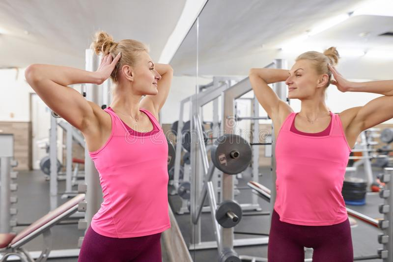 Young beautiful athletic woman blonde in gym looking in the mirror. People beauty fitness sport healthy lifestyle concept royalty free stock photo