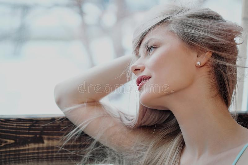 Young beautiful athletic woman blonde in sportswear sitting by the window of a cafe against the background of a wooden royalty free stock photography