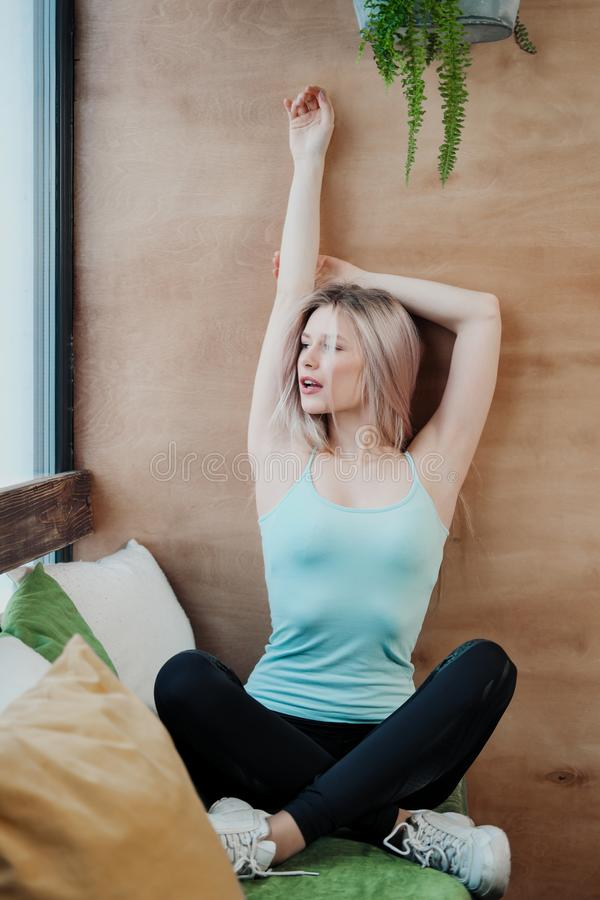 Young beautiful athletic woman blonde in sportswear sitting by the window of a cafe against the background of a wooden royalty free stock image
