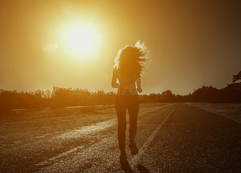 Young, beautiful, athletic woman with long curly hair in the morning runs on the background of sunrise. royalty free stock image