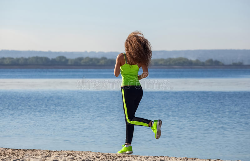 Young, beautiful, athletic woman with long curly hair in the morning runs on the beach, by the lake. royalty free stock photo