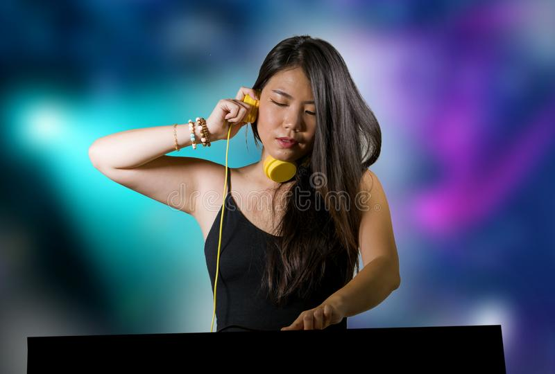 Young beautiful and attractive Asian Chinese DJ woman remixing music at night club wearing headphones isolated on flashes and. Lights background in clubbing stock photos