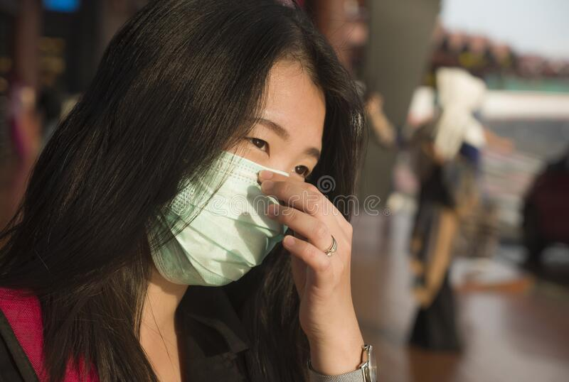 Young beautiful and attractive Asian Chinese student at airport wearing protective facial mask against China Coronavirus epidemic. Outbreak spreading breathing royalty free stock photography