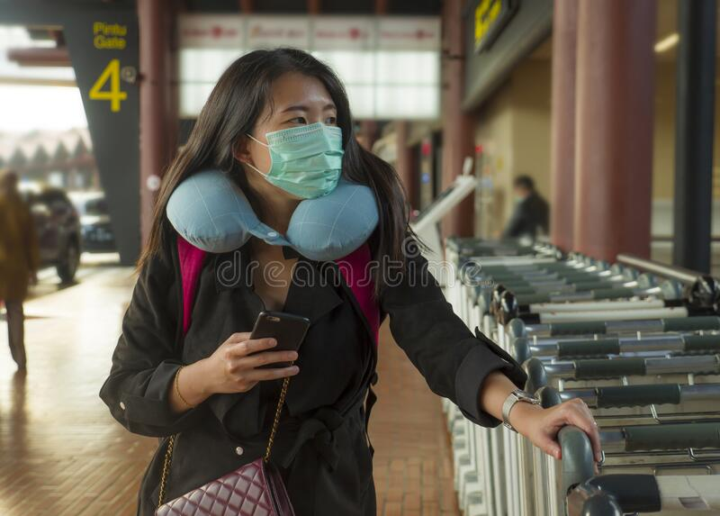 Young beautiful and attractive Asian Chinese student at airport wearing protective facial mask against China Coronavirus epidemic. Outbreak spreading breathing stock image