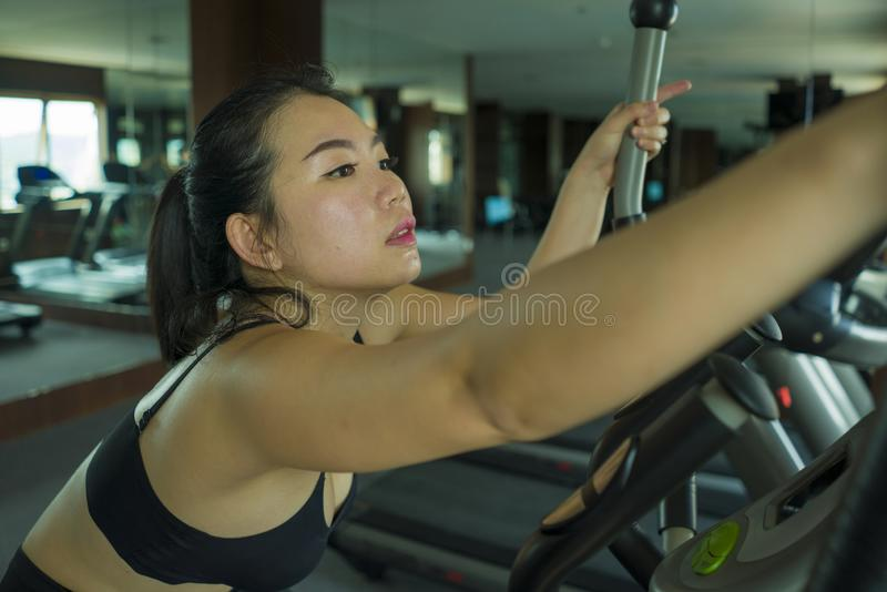 Young beautiful and attractive Asian Chinese woman training at hotel gym or fitness club working hard doing cardio elliptical. Workout in sport and healthy royalty free stock photo