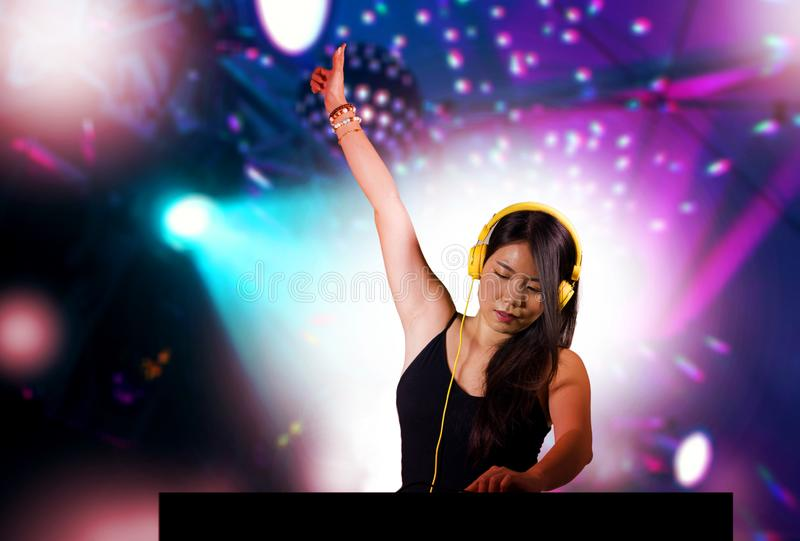 Young beautiful and attractive Asian Korean DJ woman remixing music at night club wearing headphones isolated on flashes and laser. Young beautiful and royalty free stock photos