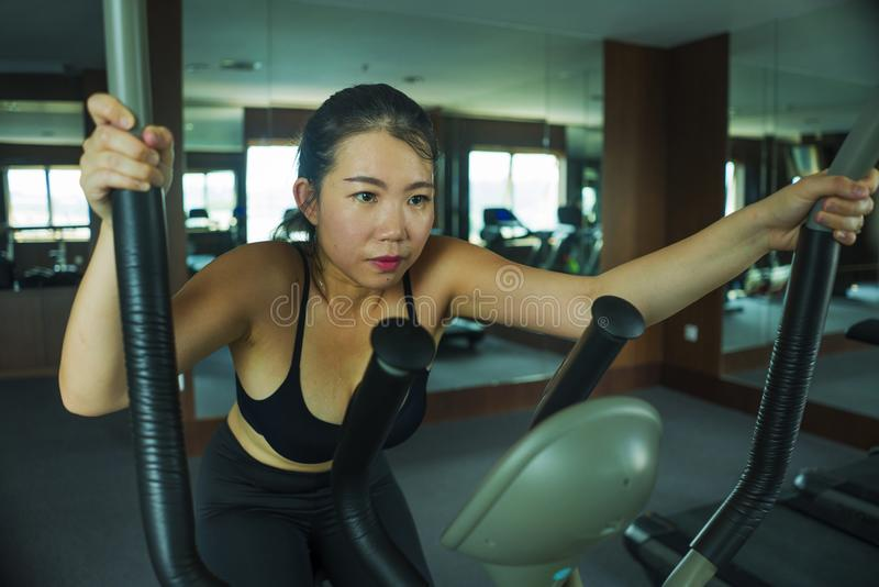 Young beautiful and attractive Asian Korean woman training at hotel gym or fitness club working hard doing cardio elliptical. Workout in sport and healthy royalty free stock image