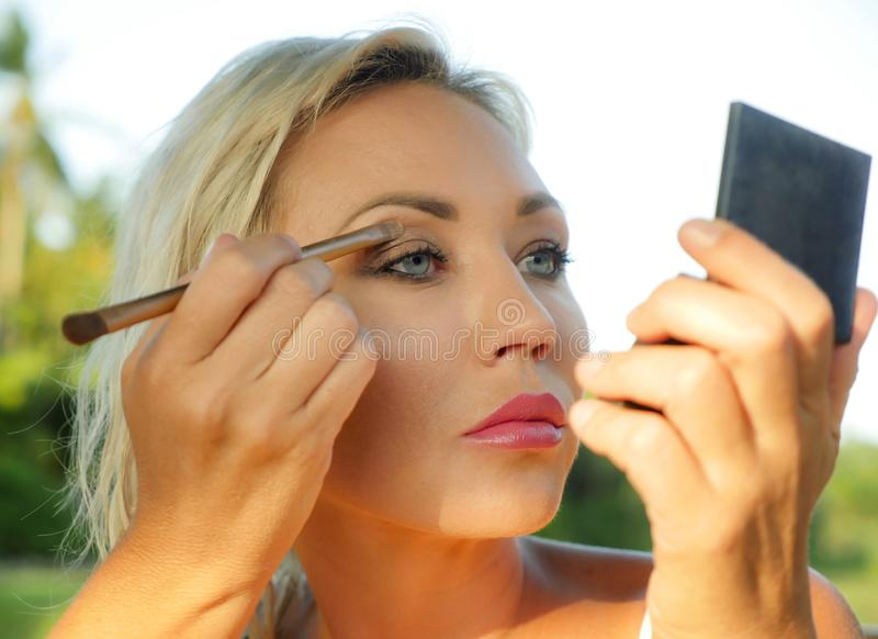 Young beautiful and attractive blond woman with blue eyes retouching makeup with brush applying eyeshadow holding small mirror in royalty free stock image