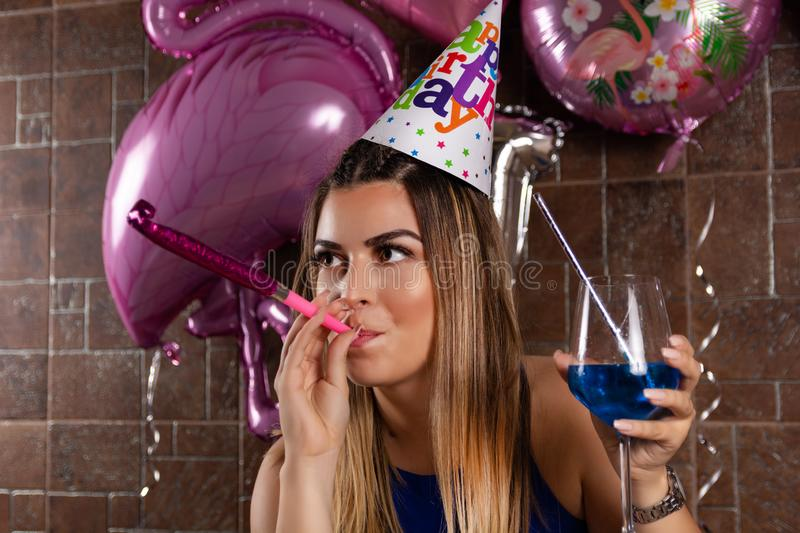 Happy young woman with musical blowouts and cocktail blue lagoon in hand and cap on the head celebrates her birthday stock photos