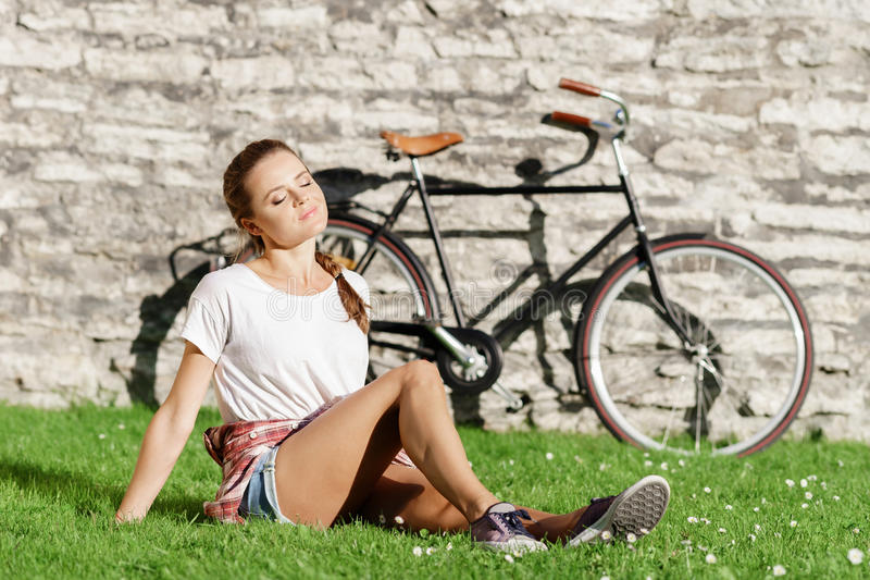 Young, beautiful attractive hipster girl relk.axing in park. Holiday, vacation, traveling concept stock photography