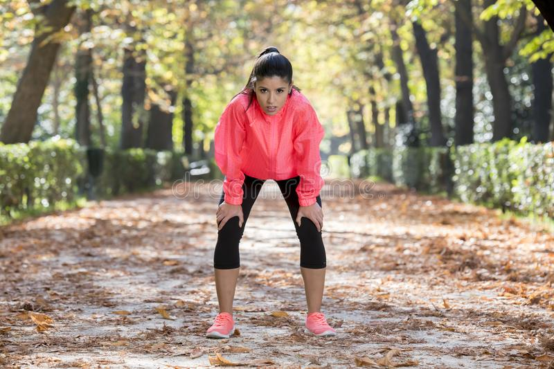 Attractive sport woman in runner sportswear breathing gasping and taking a break tired and exhausted after running workout on Autu. Young beautiful and royalty free stock image