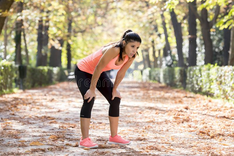 Attractive sport woman in runner sportswear breathing gasping and taking a break tired and exhausted after running workout on Autu. Young beautiful and stock images