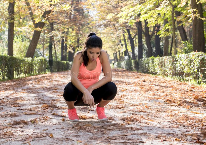 Attractive sport woman in runner sportswear breathing gasping and taking a break tired and exhausted after running workout on Autu. Young beautiful and royalty free stock photos