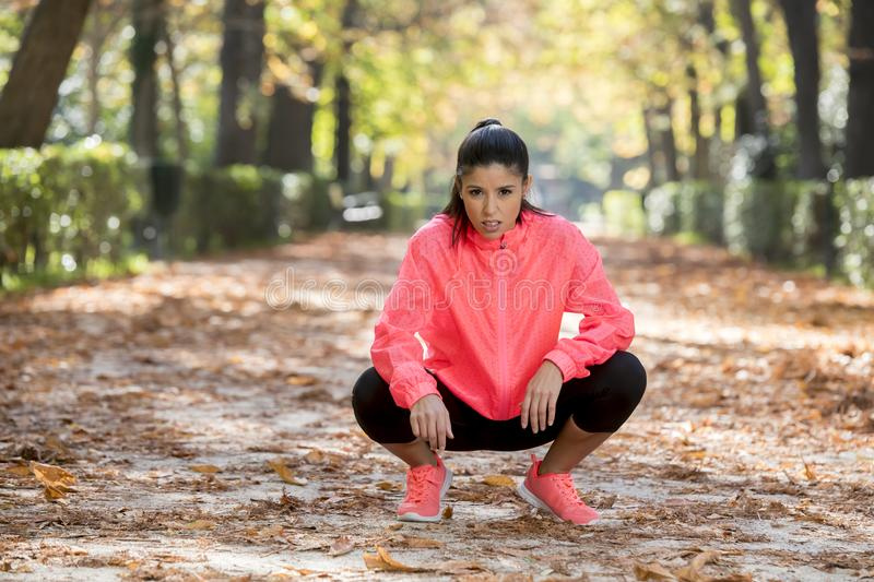 Attractive sport woman in runner sportswear breathing gasping and taking a break tired and exhausted after running workout on Autu. Young beautiful and royalty free stock photo