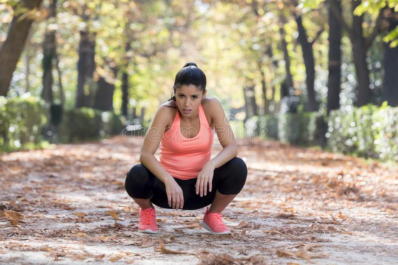 Attractive sport woman in runner sportswear breathing gasping and taking a break tired and exhausted after running workout on Autu. Young beautiful and royalty free stock photography