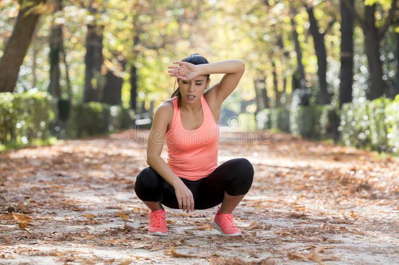 Attractive sport woman in runner sportswear breathing gasping and taking a break tired and exhausted after running workout on Autu. Young beautiful and stock photography