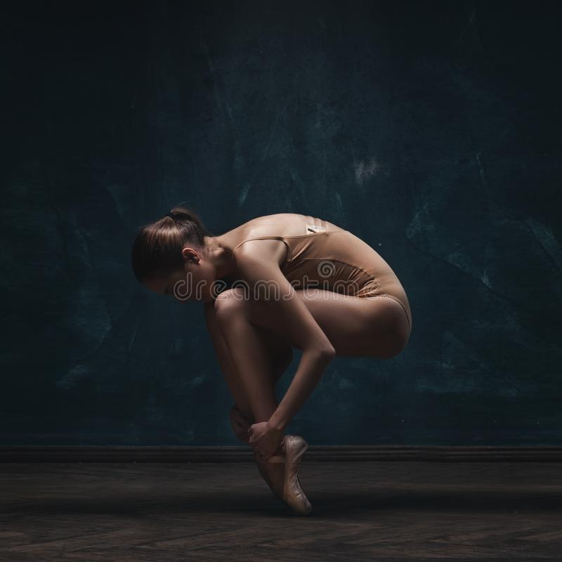Young beautiful ballet dancer in beige swimsuit. Posing on pointes over dark grunge background royalty free stock image