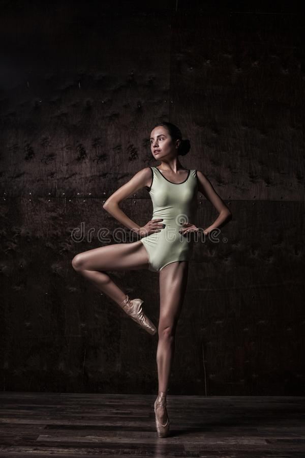 Young beautiful ballet dancer in green swimsuit posing on pointes. Over dark grunge background stock photo