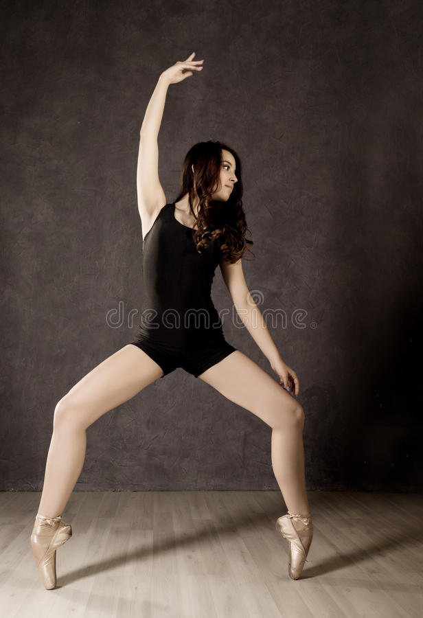 Young beautiful ballet dancer in pointe shoes, dancing in a dark background stock photo
