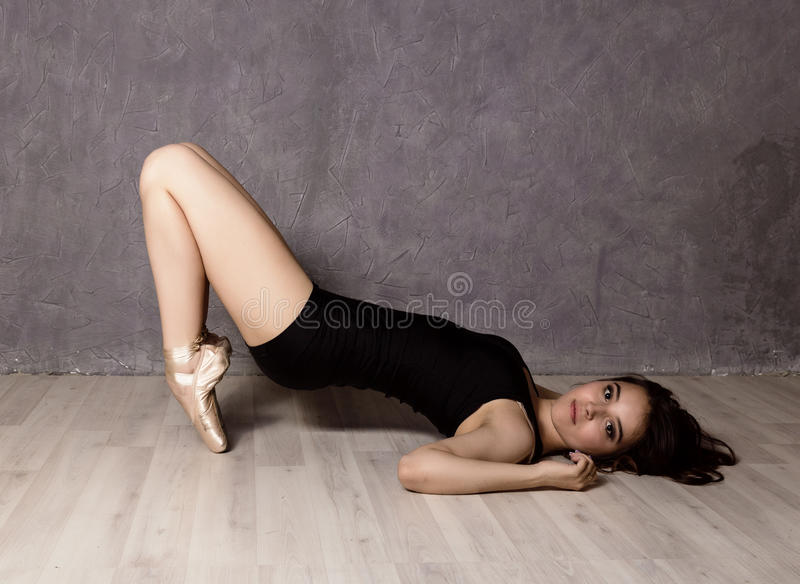 Young beautiful ballet dancer in pointe shoes, dancing in a gray background.  royalty free stock images