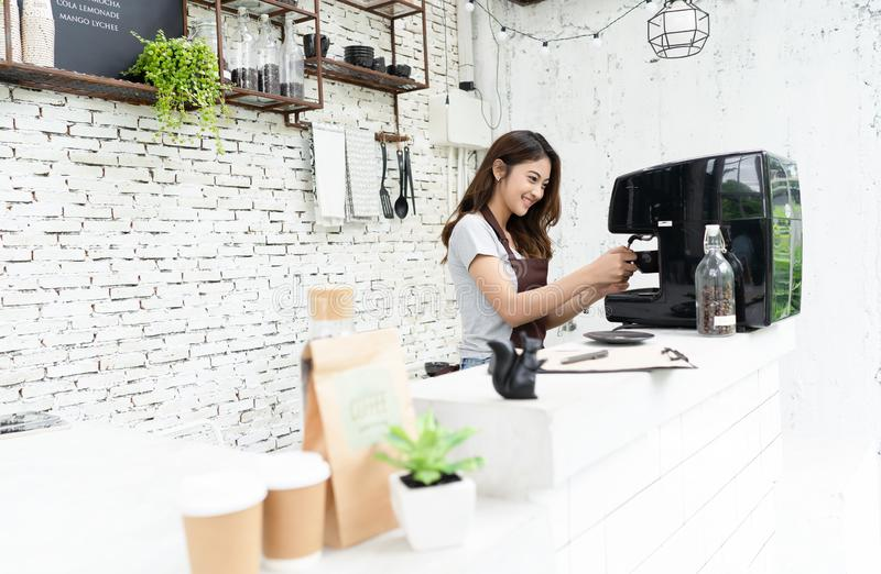 Young beautiful barista female in an apron preparing cup of coffee for customer in coffee shop. Woman startup business owner and. SME Concept royalty free stock photography