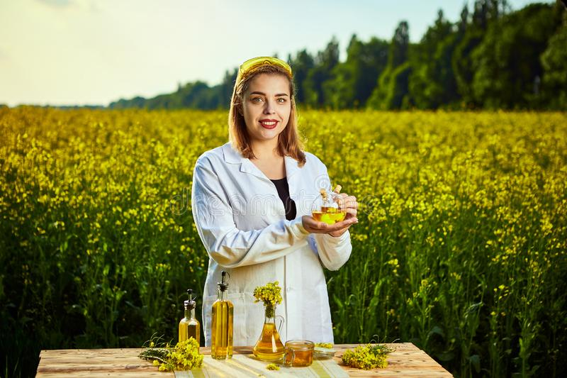 A young beautiful biologist or agronomist examines the quality of rapeseed oil on a rape field. Agribusiness concept royalty free stock images