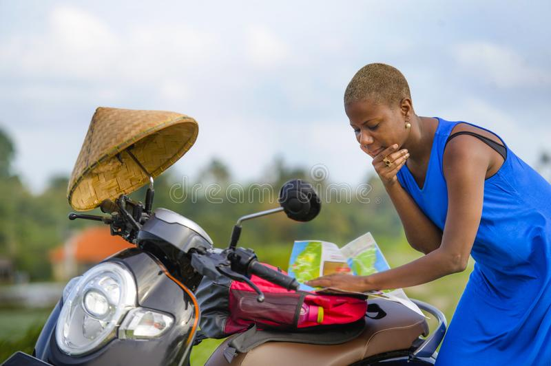 Young beautiful black afro american tourist woman with scooter motorbike looking to road map searching the way exploring fields in. Asia holidays summer travel royalty free stock images
