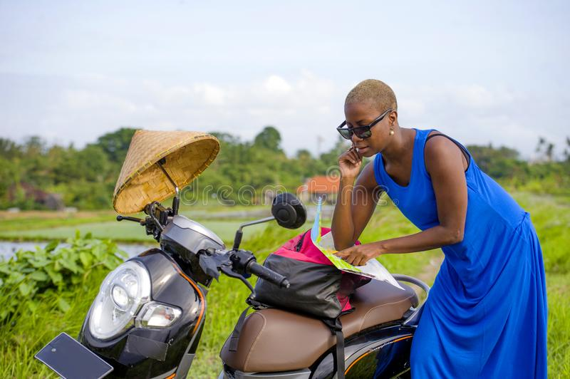 Young beautiful black afro american tourist woman with scooter motorbike looking to road map searching the way exploring fields in. Asia holidays summer travel stock image