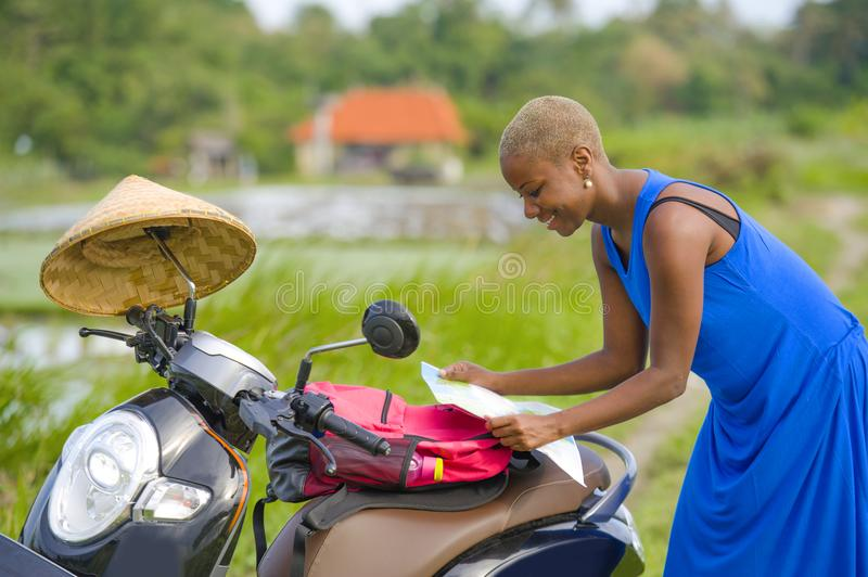 Young beautiful black afro american tourist woman with scooter motorbike looking to road map searching the way exploring fields in. Asia holidays summer travel stock images