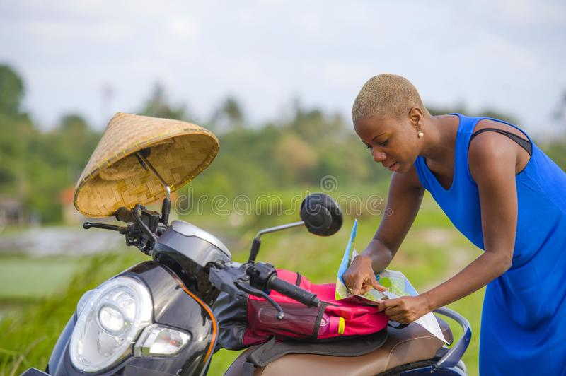 Young beautiful black afro american tourist woman with scooter motorbike looking to road map searching the way exploring fields in. Asia holidays summer travel royalty free stock photo