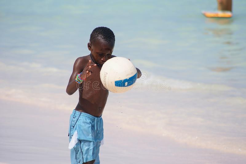 Young beautiful black boy  in blue shorts  playing football on the sunny caribbean beach just after swimming .Bavaro beach,Punta royalty free stock photo