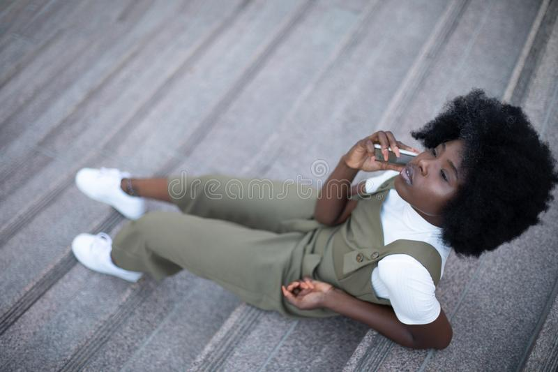 Young and beautiful black girl talking on her cell phone sitting on the grey concrete stairs stock photo