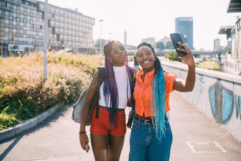 Young beautiful black sisters outdoor backlight using smartphone taking selfie royalty free stock photo