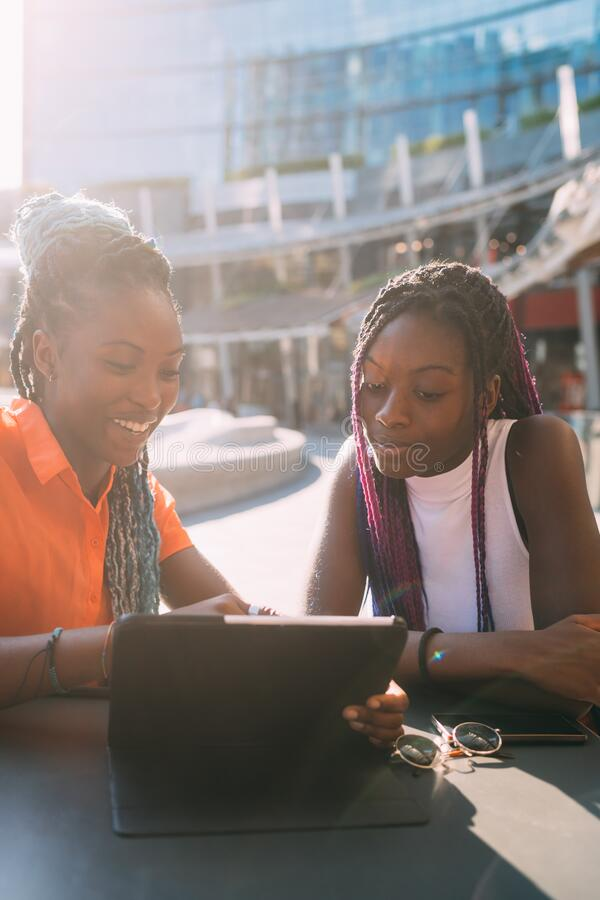 Young beautiful black sisters outdoor backlight using tablet stock images