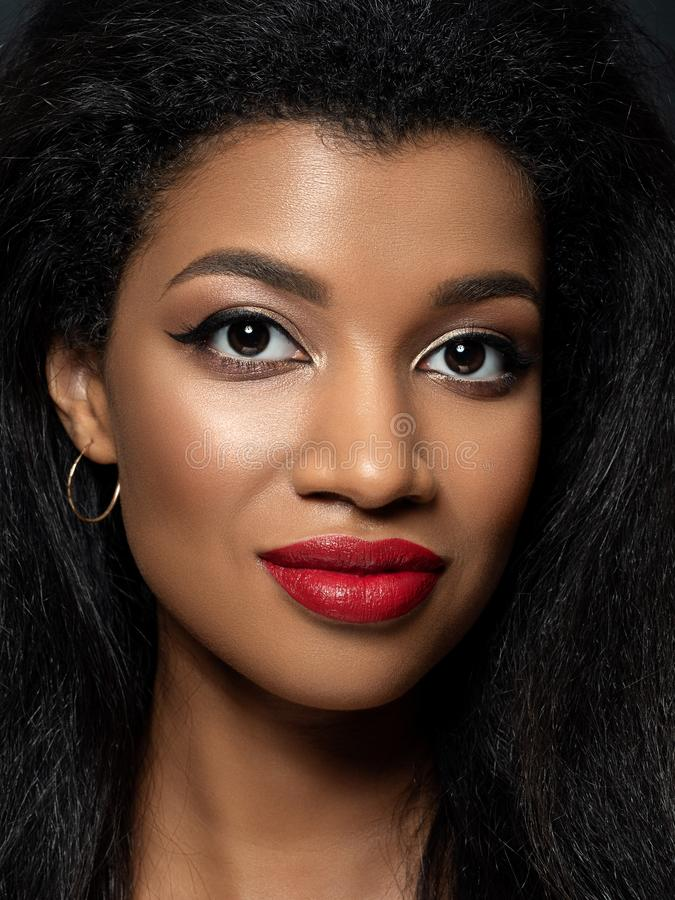 Young beautiful black woman with evening makeup. Portrait of young beautiful african smiling woman with evening make up. Red lips, rose gold eyeshades and black stock photo