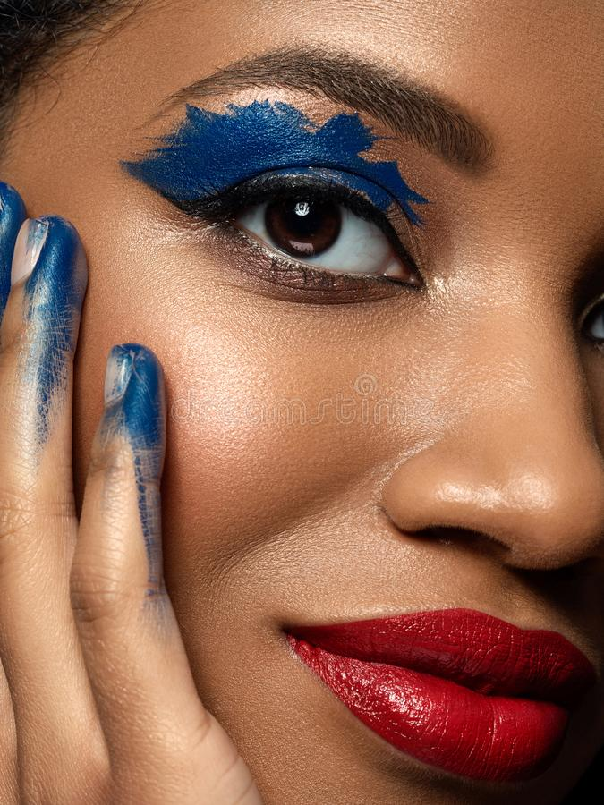Young beautiful black woman with fashion makeup. Portrait of young beautiful african woman with fashion make up. Red lips, blue eyeshades and black eyeliner stock images