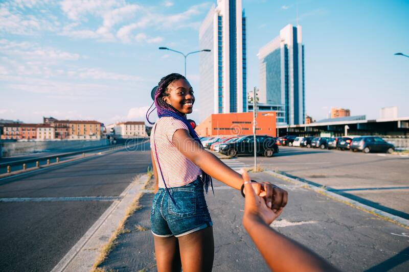 Young beautiful black woman outdoor holding hand walking on the road, smiling. Young beautiful black women outdoor holding hand walking on the road, smiling stock photography