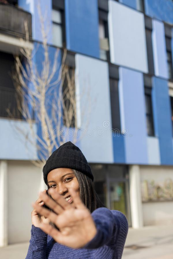 Young beautiful black woman standing outdoors in the city using a phone while looking camera and forbids stock photo