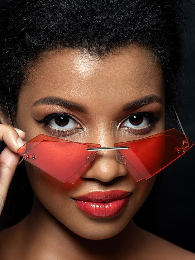 Young beautiful black woman wearing red sunglasses. Young beautiful black woman looking over modern fashion red sunglasses. Red lips and rose gold eyeshades stock image