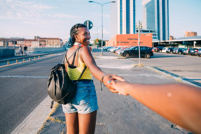 Young beautiful black woman outdoor holding hand walking on the road, smiling royalty free stock images