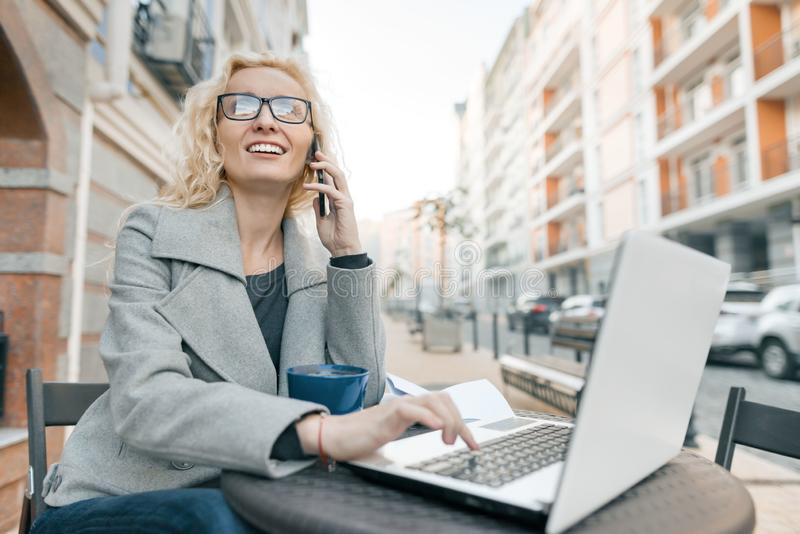 Young beautiful blond businesswoman in glasses in warm clothes sitting in an outdoor cafe with laptop computer drinking cup of royalty free stock photography